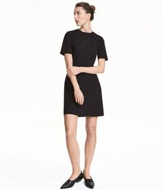 Black. Fitted, knee-length dress in woven stretch fabric. Short sleeves, seam at waist, and concealed back zip. Lined.