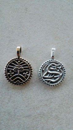 Vedhæng Wodan monster-Ribe mønt Sølv: 180 kr.  Bronze: 75 kr.  ø 18 mm  I DK er fundet 228 sølvmønter, heraf  210 i Ribe, der i 700-årene blev brugt  som betalingsmiddel. Originalen er 11 mm stor og vejer 1 g og er en af de ældste mønter fremstillet i DK. På den ene side ses en mandsmaske  med strittende hår og stort skæg. På  bagsiden ses et dyr, hvis hoved er  bøjet bagover ryggen og som bider i  sin egen hale.