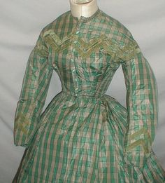 A beautiful 1860's Civil War era two tone green plaid silk dress.  The bodice and sleeve cuffs are trimmed with bands of green velvet trim. The bodice is lined with cotton and has a front hook and eye closure. The green satin buttons are decorative. The armscyes and waist are piped. The skirt is fully lined with cotton.  The dress is in very good and sturdy condition.  Bust 32 Waist 22 Front Skirt length 40 Back length 44 Width at hemline 158.  Ebay