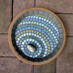 A mosaic bird bath for the garden with a design giving the impression that a pebble has been dropped in and is creating ripples of colour across the surface. Glass and irridescent tiles are used add to the watery effect of the design. Could be used indoors as a decorative dish too. 23cm diameter.