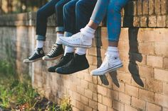 Friends take picture of all their shoes and legs hanging on the side of a brick wall.