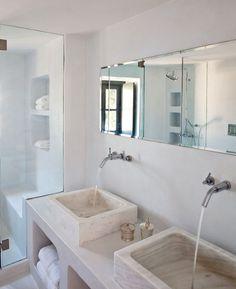 Lavabos en marmol. Grifería en pared. Todo en distintos tonos de blanco.