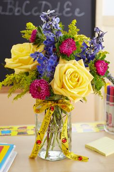 Bring your new teacher a cute back to school floral arrangement to start the year off right! 1800Flowers Floral Lifestyle Expert Julie Mulligan shows you how with hand picked fresh flowers in a mason jar vase and school themed ribbon!