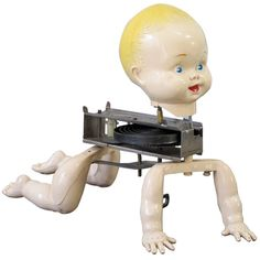 Mechanical Crawling Baby Doll   United States   c. 1950's   Key wind metal mechanism attached to the joined pair of plastic arms and legs with painted baby head on top. I have collected robotics and have searched for a mechanical doll from the 1950s for some time. A tin cover went over the motor