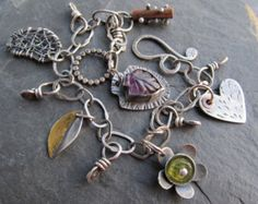 Every part of this eclectic charm bracelet was made by hand by me including the chain and every charm. I used a variety of metalworking techniques such as wire wrapping, piercing, stamping, soldering and riveting. the chain is a mixed up concoction of links and connectors in different textures and sizes. I added two little gemstones (genuine pink Sapphire and green Tourmaline) just for a drop of color. This bracelet measures about 8 inches in length. Please let me know if you need it…