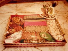 1stchoicegift: Theme: Royalty (Karva chauth platter) Pink tray with Mirror work border and pearl handle decoration. A elegant golden flower bunch with mor pankhi and pearl boundary. Pearl brooch, a pair of golden small flower with pearl bud and pink brooch inside decor. highlighted with name Product available at: https://www.facebook.com/1stchoicegift