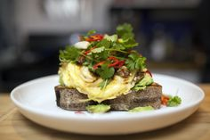 Grilled sourdough, sausage, soft scrambled eggs, fresh herbs, and mashed avocado: This dish might be the one thing that could get us out of bed right now.