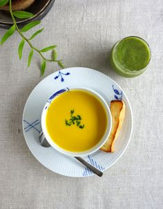 Kabocha squash soup, a piece of bread and green smoothie