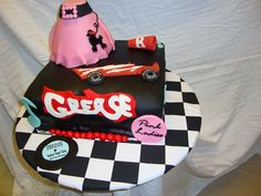 Grease Birthday Cake - Birthday cake made for Grease lover (which I also happen to be.)  Milk chocolate cakes filled with chocolate ganache and iced in chocolate buttercream.  Poodle skirt is RKT iced with chocolate buttercream and covered in some very tempermental fondant.  The red and black fondant is Satin Ice; the rest is MMF that I made.  All items are combos of fondant and gumpaste.  Great fun to make, but had some issues.  Thanks for looking!
