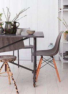 Grey Eames chair with natural wooden dowel legs. Modern dining setup.
