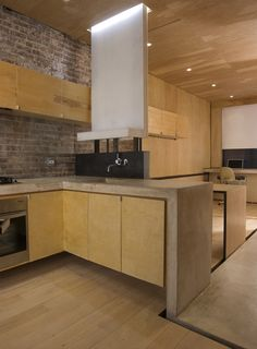 """The apartment, measuring just over 400 square feet, opens into the kitchen, which architectural designer Alan Y. L. Chan outfitted with a Dornbracht faucet and a sink of his own design. The black steel backsplash doubles as the back of a built-in bench on the other side. A concrete """"ribbon"""" serves as the main design concept and the countertop, and continues throughout the apartment. A built-in LG refrigerator is located just across the concrete floor at right. Image courtesy Brian Riley…"""