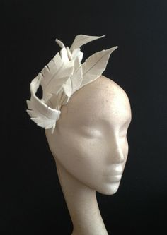 Ivory peachbloom felt feathers with silver stitching, curled round Can be mounted on a headband or with little loops for Kirby grips so it can go anywhere on the head. Would be a great winter bridal headpiece. It can be made in other colours and made to sit at either side of the head.