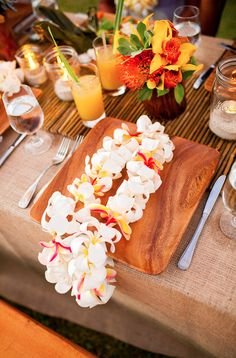 Fresh flower leis are a Hawaii wedding tradition. This modern luau on Kauai was the perfect Welcome Dinner for guests. By Moana Events.