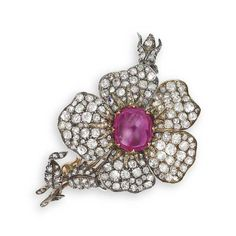 A STAR RUBY AND DIAMOND BROOCH. Designed as an old mine-cut diamond flower brooch, centering on a cabochon star ruby weighing approximately 8.48 carats, mounted in 18k rose and white gold, 6.7 cm wide. Accompanied by report no. 2135935528 dated 18 October 2011 from the Gemological Institute of America stating that the 8.48 carat natural star ruby is of Burma (Myanmar) origin, with no indications of heating