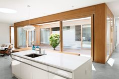 From the kitchen and living room you're well connected to the courtyard and the rest of the house. The trim and accents are white oak; the kitchen is by Leicht.  Photo by: Jessica Haye and Clark Hsiao