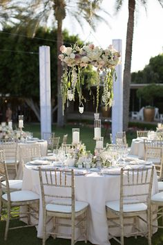 For the dinner service, guests took their seats at round tables swathed in creamy linens on chairs featuring a distressed finish. #receptiondecor Photography: Stephanie Fay Photography. Read More: http://www.insideweddings.com/weddings/sophisticated-garden-inspired-wedding-in-phoenix-arizona/659/