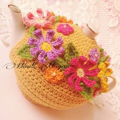 A truly terrifying tea-cosy. Those knit flowers could eat your face off.