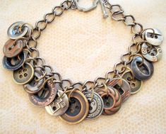 A variety of vintage buttons in this bracelet which has a rustic feel. Brass, copperplated,and silvertone metal buttons all form a unique bracelet design. The buttons are attached to the link chain with jumprings. The chain is also mixed metals of brass and gunmetal finish and ends with a lobster clasp. $30
