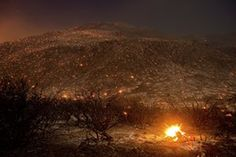 Embers from a wildfire smolder along Lytle Creek Road near Keenbrook, California