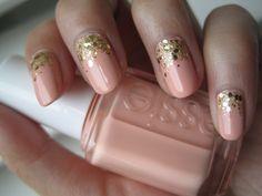 Uñas pintadas en color nude con brillos dorados