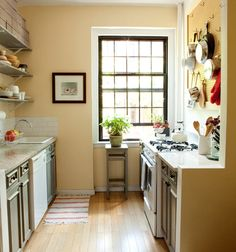"""Image above: One of our favorite rooms in the apartment is our sunny kitchen, painted in Cornsilk by Benjamin Moore. The large framed peg board holds many of our pots and pans and helps to keep things organized since we don't have a pantry. Our wooden shelves and cabinetry are stained with a French country-inspired light blue.""   Karen wise/Chandler Kauffman on #designsponge"
