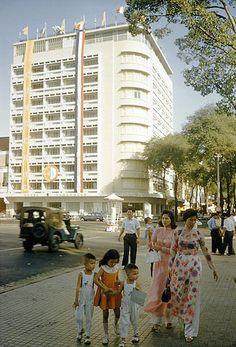 Women dressed in ao dai stroll down the street with their small children, Saigon, Vietnam, 1961, photograph by Wilbur E. Garrett.