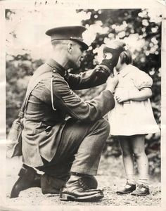 1939- British soldier helps a small girl adjust her gas mask as soldiers wives and children from the married quarters went through the army gas chamber at the Royal Artillery barracks, Woolwich, London, to see whether their gas masks were satisfactory in every way.