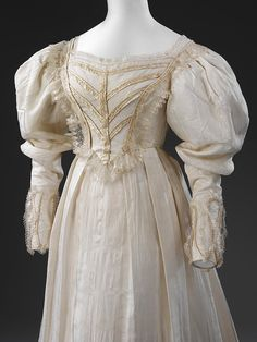1828 bodice -- London, Britain -- White silk wedding dress with detachable sleeves, trimmed with pleated bands of gold-coloured silk satin, white silk satin ribbon, hand-made silk blonde lace, and lined with cotton. ___ Has a matching pelerine made of silk, partially lined with silk. ___ Wedding dress' hem's circumference is 276 cm.