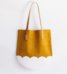 Spread some springtime cheer with this adorably printed suede tote bag. It's crafted of soft, yellow gold suede and fitted with durable vegetable tanned leather straps, to carry all of your everyday necessaries with room to spare. The tote is curved on the bottom, just like a tulip bloom, and it's printed with a white scalloped pattern along the base, for a colorblock effect.