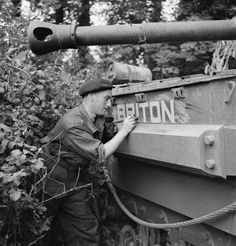 Trooper E. McGuiness, gunner of a Churchill tank of 'B' Squadron, 107th Regiment Royal Armoured Corps, 34th Tank Brigade, touching up the name 'Briton' on the side of its hull, 17 July 1944.