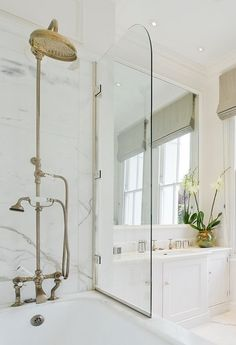 Love the seamless blend of contemporary and traditional in this bathroom featuring a wonderfully weathered Perrin & Rowe shower fixture juxtaposed with a free-swinging glass door, classic white cabinets, a sunk-in mirror, and roman shade. You'll love this space forever.