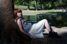 Side view of young woman resting under a tree stock photo