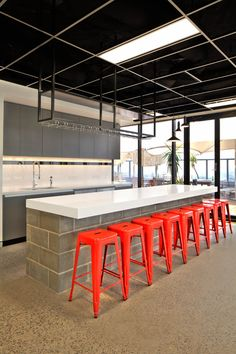 The Bold Collective | Traffik | Kitchen Breakout: open ceiling grid, black ceiling, red tolix stool, subway tiles, polished concrete, besser bricks, glass cabinet, pendant lights