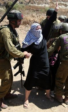 Israeli soldiers arrest prominent activist Nariman Tamimi for taking part in a peaceful protest against the theft of Palestinian land by Israel, on August 24, 2012. The soldiers used force to hold back her young daughters who were trying to intervene. Getty Image.