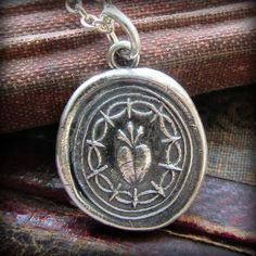 Handmade using an antique seal, this pendant depicts a flaming heart which is symbolic of ardent love and undying affection.