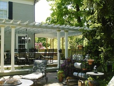 1823 House with pergola - I like how this connects the house to the patio, and bends around the house, not just in a square shape.