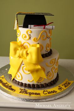 Large Bow & Cap #23Graduation  This two-tier cake is iced in buttercream and accented with our popular swirls and dots. The yellow fondant bow makes a great focal point. It is topped off with a graduation cap and diploma. This cake can be changed to match any school colors.