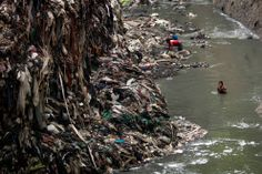 A youth who goes by the name Baluquita (15) searches for scrap metal in contaminated water next to a mountain of garbage. (Rodrigo Abd/Associated Press)