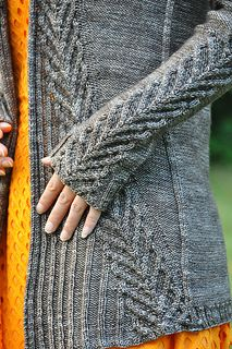 """""""Ink"""" is the perfect cardigan to slip on when the balmy days of summer transition to the chilly days of autumn. Named for the color of the yarn, it is also a reminder that autumn brings with it the beginning of a new school year. Knitted in fingering yarn and reverse stocking stitch from the collar down, the cables on the garment bring to mind the V's of birds flying south for the winter."""