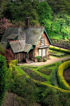 A beautiful little cottage surrounded by such lush green grounds.