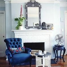 killer blue velvet chair, love the blue walls and white brick fireplace.  great accessories! super cute side table.