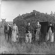 women of the west standing next to a mud house (sod home), with which every settler used to build their homes, since there was no trees with which to build homes on the prairie. Biddy Craft