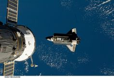 Soyuz in foreground and Discovery center during STS-119.