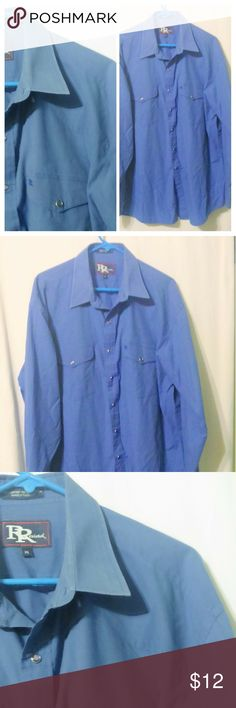 """RESISTOL RODEO Pearl-Snap  Western Blue Shirt This men's Western shirt is made by Resistol and is a size XL. The shirt is done in a dusty blue cotton blend and features pearl snaps down the front and on the cuffs. I can't quite tell but it looks like there may be a bit of wash wear on the collar, not noticeable but wanted to bring it up. Measurements are: Chest 54"""", sleeves 25"""", length 33"""". Resistol Shirts Casual Button Down Shirts"""