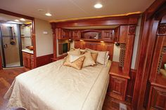 In the bedroom, built-in cabinetry with impressive detail surrounds the comfortable queen bed. Mobile Command Center, Luxury Fifth Wheel, Tumbled Marble Tile, Fiberglass Shower, Rv Trailers, Theater Seating, Pocket Doors, Mobile Home, French Country Decorating