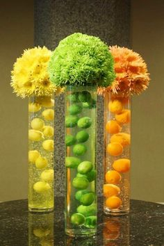 """""""Citrus Surprise"""" Cool icy and refreshing. A gelatin like material suspends fresh citrus fruits in tall glass cylinders. Spheres of spider mums top these citrus coolers. So cute for centerpieces. Flower Centerpieces, Table Centerpieces, Wedding Centerpieces, Wedding Decorations, Table Decorations, Colorful Centerpieces, Wedding Table, Wedding Art, Wedding Ideas"""