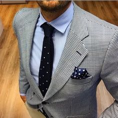 Pair a white and black houndstooth coat with cream casual trousers to look classy but not particularly formal.   Shop this look on Lookastic: https://lookastic.com/men/looks/blazer-dress-shirt-chinos/21402   — Light Blue Vertical Striped Dress Shirt  — Black Knit Tie  — White and Black Houndstooth Blazer  — Navy Polka Dot Pocket Square  — Beige Chinos