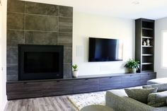 Asymmetrical fireplace and TV wall with built-in cabinetry storage drawers. Designed by Jillian Lare Interior Design.