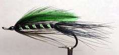 CoastEmerald by Charlie Dickson _ Hook: Up eye salmon hook. Tag: Oval green tinsel. Tail: Black dyed pheasant rump feathers wound and pulled back. Rib: Green flat braid and oval silver tinsel. Body: Black seal dibbing or substitute. Collar: Black dyed pheasant rump. Wing: Two green hackles enveloped by two black hackles. Head: Black.