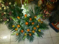 Rosas naranjas sobre un fondo verde y gladiolos blancos.
